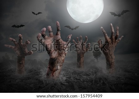 Halloween background with zombie hand rising out of the ground - stock photo