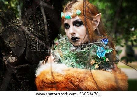 Halloween beautiful girl gnome. In the branches of an old tree - stock photo