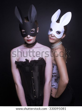 Halloween. Black and white rabbits. Two young women in masks. - stock photo