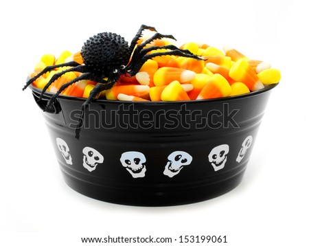 Halloween bowl filled with candy corn and toy spider over white - stock photo