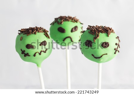 Halloween cake pops with holiday decor on white background. - stock photo