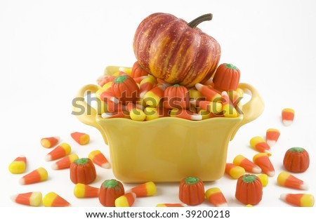 Halloween Candy Corn in a yellow candy dish with a little pumpkin on top, horizontal with copy space, isolated on white background - stock photo