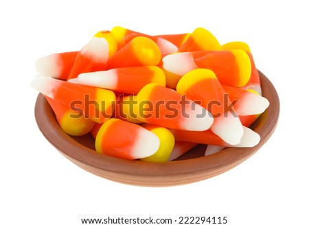 Halloween candy corn kernels in a small bowl on a white background. - stock photo