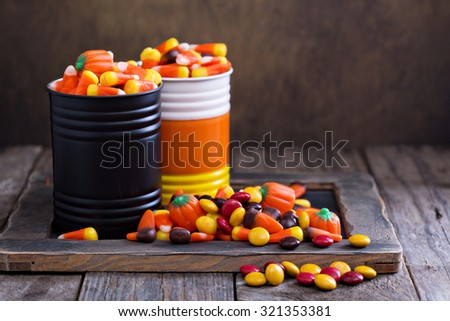 Halloween candy in small tins on brown rustic table - stock photo