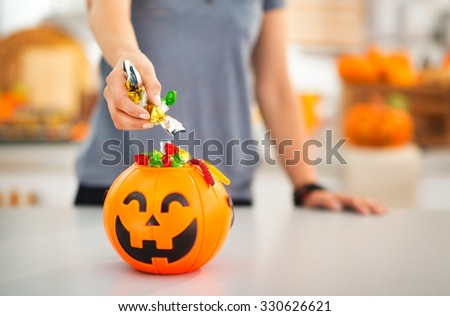 Halloween candy is never too much! Closeup on woman putting trick or treat candy in halloween Jack-o-Lantern bucket. Traditional autumn holiday - stock photo