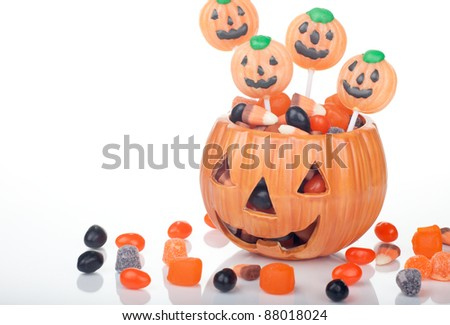 Halloween candy scattered around and in a pumpkin shaped bowl - stock photo