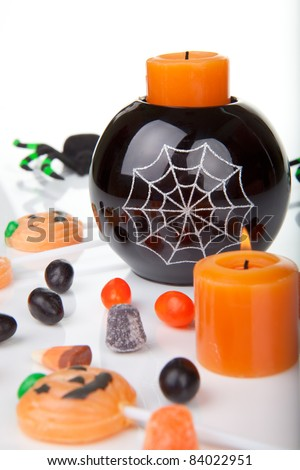 Halloween candy scattered around, candles, and spiders. - stock photo