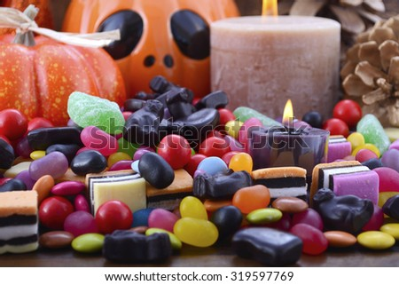Halloween Candy with pumpkins, Jack O Lantern, candles and bats on dark wood background.  - stock photo