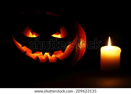 Halloween carved pumpkin and candle on black background - stock photo