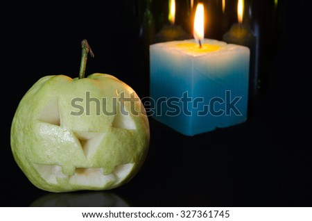 Halloween Carving Guava in the Night with Candle Light Background Texture