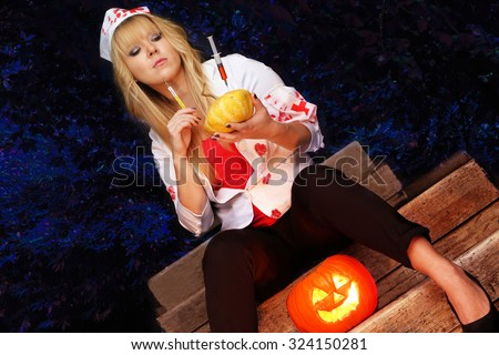 halloween celebration - pretty girl dressed as halloween nurse wearing a blood stained jacket holding a pumpkin and a syringe and a dark forest background. - stock photo