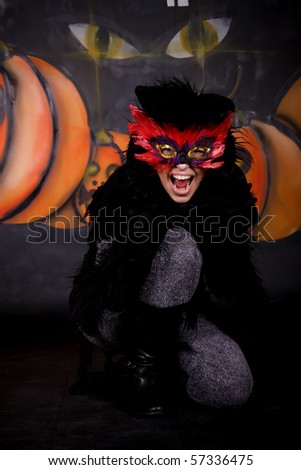 Halloween character, female cat costume.    Studio shot, painted themed background.
