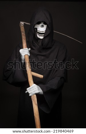 Halloween character: grim reaper. Studio portrait on black background - stock photo