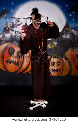 Halloween character, man in creepy pose.    Studio shot, painted themed background.