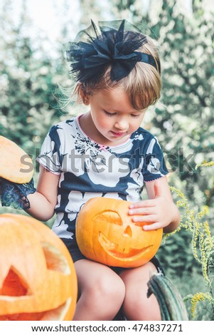 Halloween. Child dressed in black with jack-o-lantern in hand, trick or treat. Little girl looking on pumpkin in the wood, outdoors. Toned photo.