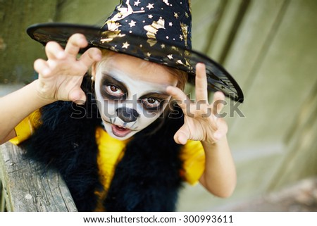 Halloween child with painted face and frightening expression - stock photo