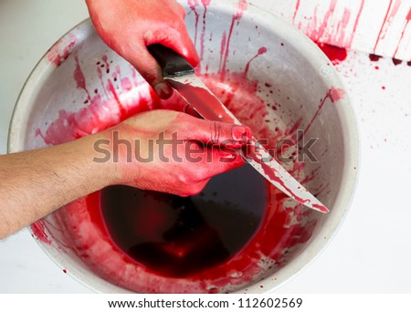 Halloween concept : Hand in blood with knife  on a white background