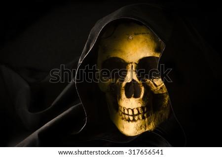 Halloween concept of scary skull head in black hood - stock photo