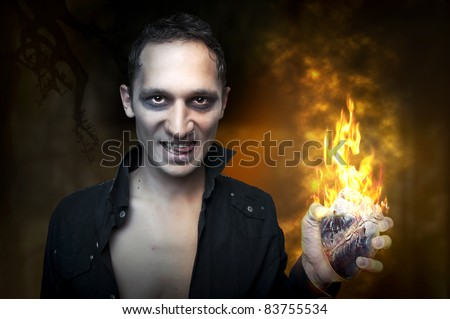 Halloween concept. Portrait of handsome man - night vampire, demon or zombie, holding in hand heart burn in fire - stock photo