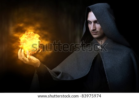 Halloween concept. Powerful Male witch or wizard with fireball in hands. Ball from fire burns - stock photo