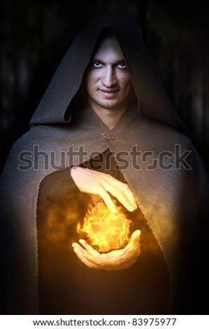 Halloween concept. Powerful Male witch or wizard with fireball in hands. Ball from fire burns