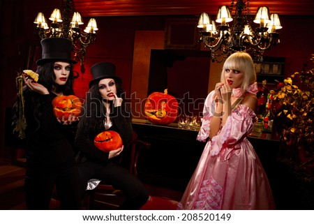 Halloween concept: sexy ladies vampire with halloween pumpkins assailing blond girl - stock photo