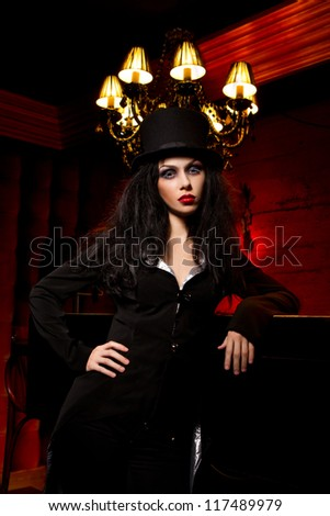 Halloween concept: sexy lady vampire next to bar over red background - stock photo