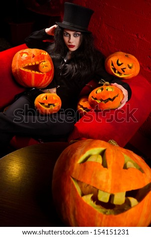Halloween concept: sexy lady vampire with halloween pumpkins over red background - stock photo