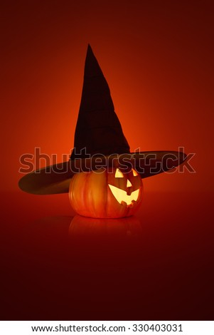 Halloween concept with a black Witches hat on a jack o lantern Pumpkin - stock photo
