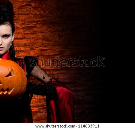 Halloween concept: young and sexy lady vampire in the dungeon - stock photo