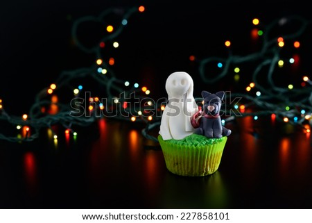 Halloween cupcake decorated with sugar ghost and black cat. - stock photo