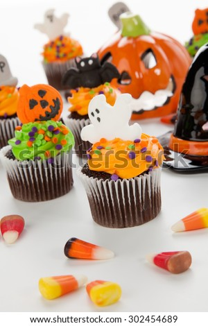 Halloween cupcake with ghost decorations surrounded by Halloween cupcakes, corn candies, and decoration.  - stock photo