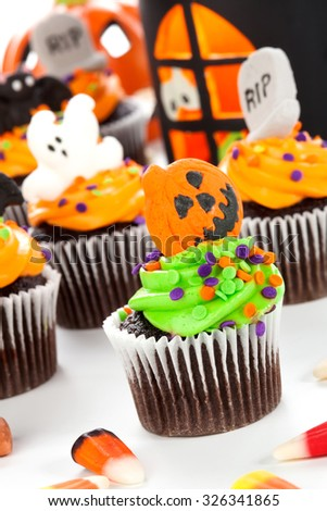 Halloween cupcake with jack-o'-lan�·tern and bat decorations surrounded by Halloween cupcakes, corn candies, and decoration.