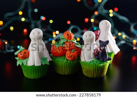 Halloween cupcakes decorated with sugar ghosts and pumpkins. - stock photo