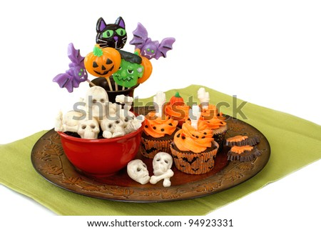Halloween cupcakes, skeleton candy, and lollipops - stock photo