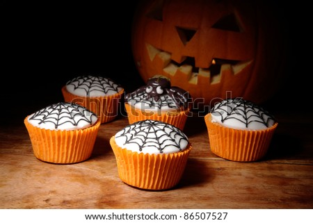 halloween cupcakes with in the background carved pumpkin. - stock photo