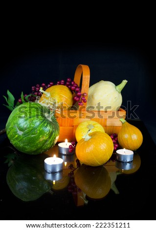 halloween decoration: group of various kind of ripe pumpkinies in light og candles on dark background - stock photo