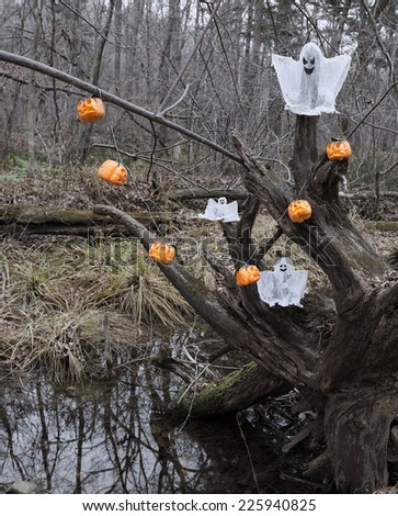 Halloween decoration in the forest, ghosts and pumpkins on the old scary tree log with water reflection - stock photo