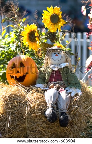Halloween decoration with scarecrow, pumpkin and sunflowers. - stock photo