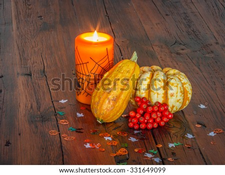 Halloween decorations, lit candle and pumpkins on a wooden table
