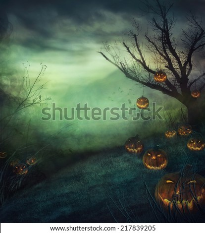 Halloween design - graveyard pumpkins. Horror background with autumn valley with woods, spooky tree and evil pumpkins. Space for your Halloween holiday text. - stock photo