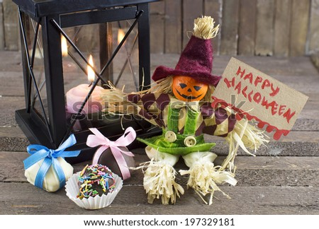 Halloween doll with holiday banner, chocolate candies and burning candle in lantern - stock photo