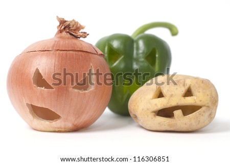 Halloween faces carved into vegetables such as onion, potato and capsicum instead of pumpkin forming special jack o lanterns. - stock photo