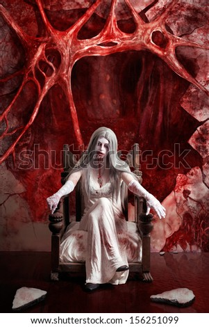 Halloween fine art portrait of a beautiful young woman dressed as dark vampire in messy white dress seated at the entrance to hell  - stock photo
