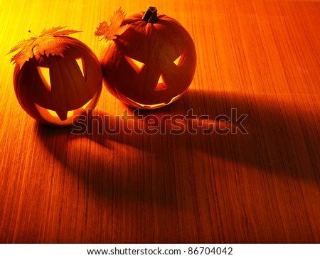 Halloween glowing pumpkins border with leaves over warm wooden background, autumn holiday, traditional party decoration, fun concept - stock photo