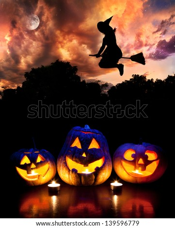 Halloween glowing pumpkins on the table and witch silhouette flying at dramatic night sky with moon - stock photo