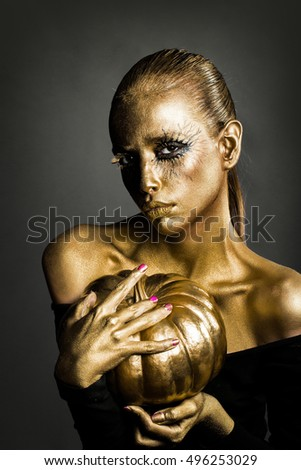 halloween golden woman or girl holding painted gold pumpkin has pretty face with makeup and body art metallized color with bare shoulders on grey background