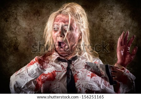 Halloween gore photo of a dead female zombie with bloody saw and amputated hand. Slasher concept