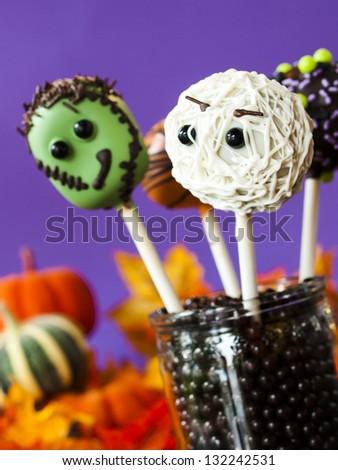 Halloween gourmet cake pops with purple backround. - stock photo