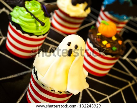 Halloween gourmet cupcakes with holiday decor black background. - stock photo